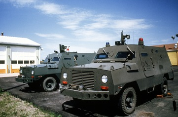 a left front view of two u.s. air force peacekeeper security police armored response_convoy trucks. the vehicles are used to patrol the base